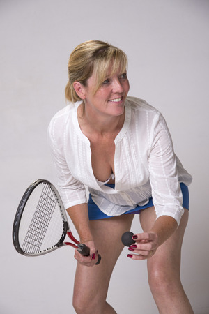 Female squash player holding ball and racquet photo