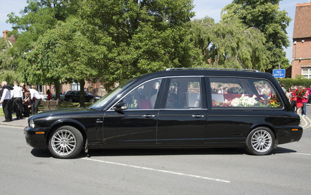 Jaguar hearse carrying a red and white coloured coffin in a funeral parade