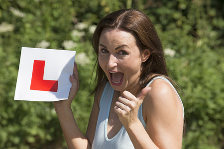 thrilling: Jubilant driver with L plate after passing her driving tes Stock Photo