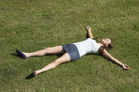 stretched out: Young woman laying on grass Stock Photo