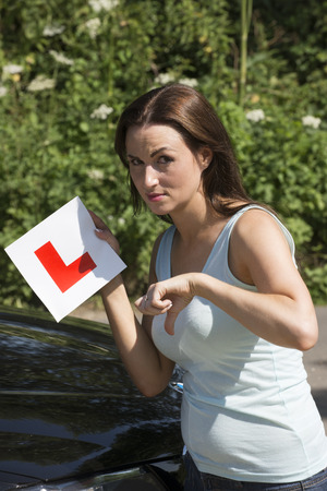 l plate: Woman driver holding L plate and thumbs down for a failure test result