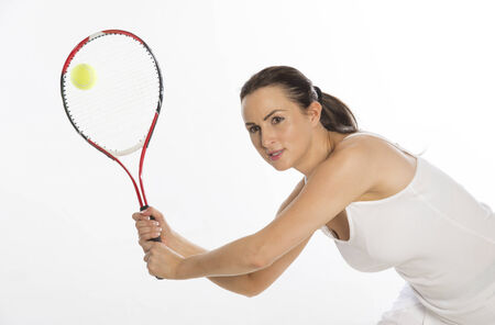 Attractive female tennis player holding the raquet with two hands photo