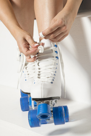quad: Roller skater tying laces on her quad wheel boots