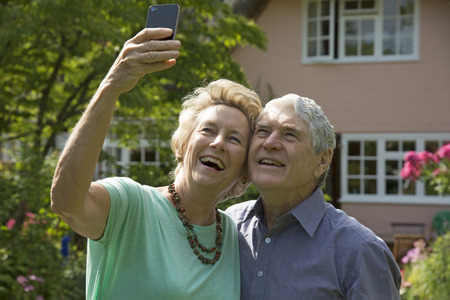 taking a wife: Elderly couple taking a selfie photo with a mobile phone