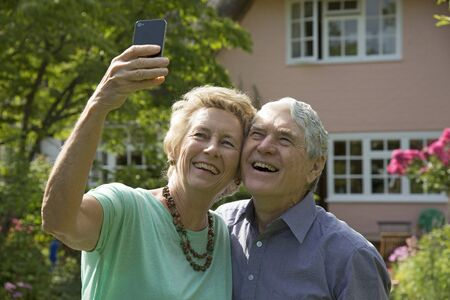 Elderly couple taking a selfie photo with a mobile phone photo