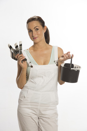 Painter wearing bib and braces overall holding brush photo