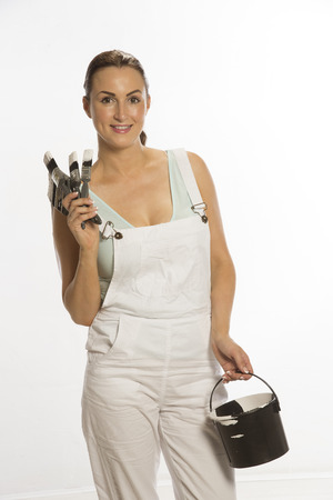 bib overall: Painter wearing bib and braces overall holding brush Stock Photo