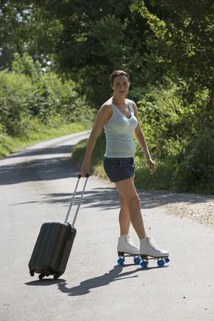 patines: Mujer joven en patines con un caso Rollalong Foto de archivo