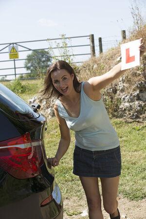 learner: Female motorist holding learner L plate