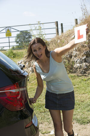 l plate: Female motorist holding learner L plate