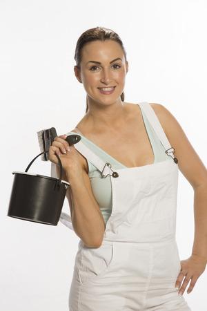 bib overall: Painter wearing bib & braces overall holding brush