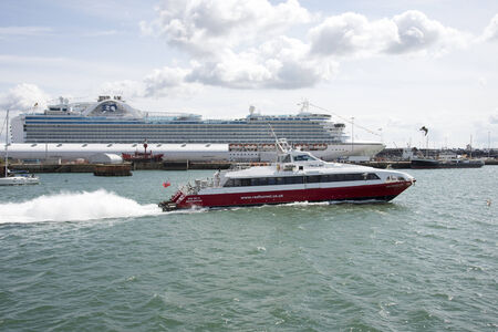 Red Jet service departing Southampton Terminal for the Isle of Wight Background is Ruby Princess