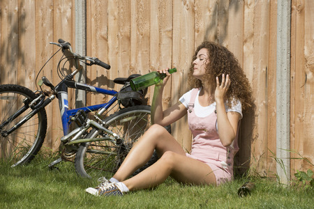 drinking alcohol: Teenage girl leaning on garden fence drinking alcohol