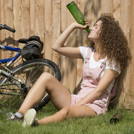 Teenage girl leaning on garden fence drinking alcohol