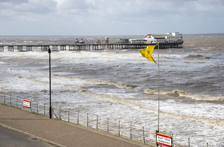 stormy waters: North Pier and a heavy sea ponding the shore at Blackpool England UK
