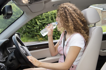 Young female driver drinking water
