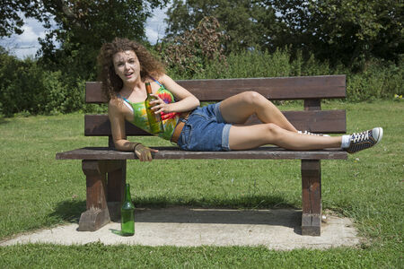 Teenage girl drinking alcohol on a park bench