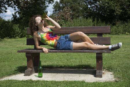 tomando alcohol: Adolescente beber alcohol en un banco de parque Foto de archivo