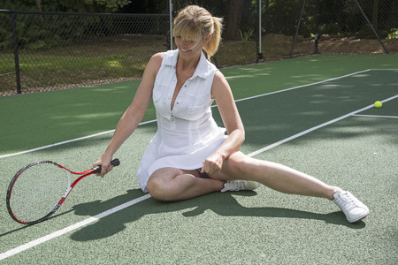 Female tennis player fallen on the court and is getting up off the ground Stock Photo