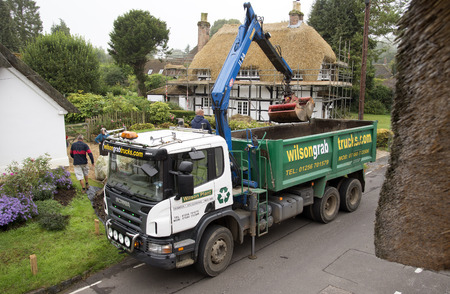 A grab truck with crane in action