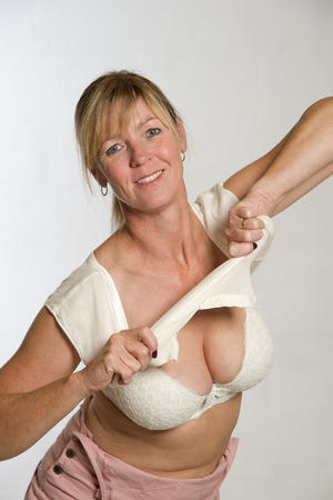 Woman getting dressed pulling shirt over her head Stock Photo
