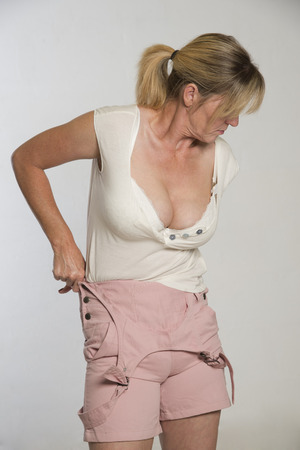 Woman getting dressed tucking shirt into bib and braces dungerees Stock Photo