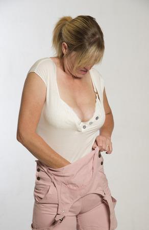 vistiendose: Mujer vestirse camisa metiendo en bib y llaves dungerees