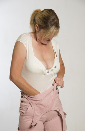 Woman getting dressed tucking shirt into bib and braces dungerees