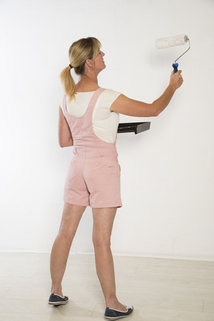 Female painter decoratorusing a paint roller photo