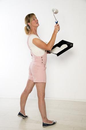 Female painter decoratorusing a paint roller photo