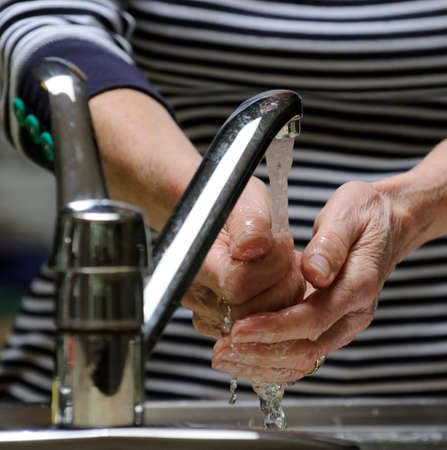 rinsing: Woman washing her hands under a running water tap