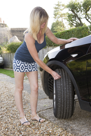 depth measurement: Woman using tyre depth gauge Stock Photo