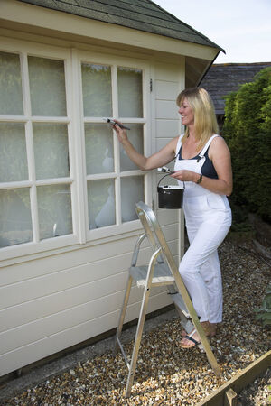 Painter decorator painting windows standing on steps photo