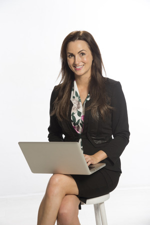 Woman with laptop computer balanced on her knee photo