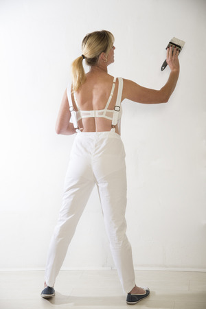 Woman in overalls painting a wall white photo