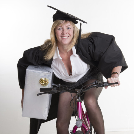 cap and gown: Mature student in cap gown holding present riding cycle Stock Photo