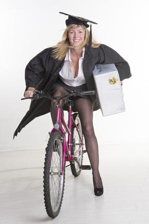 toga y birrete: Estudiante maduro en traje de tapa que sostiene el actual ciclo de paseos