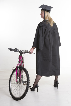 cap and gown: Mature Uni student standing in cap gown holding bicycle Stock Photo