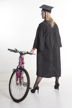 toga y birrete: Uni maduro estudiante de pie en traje de explotaci�n agr�cola del casquillo de la bicicleta