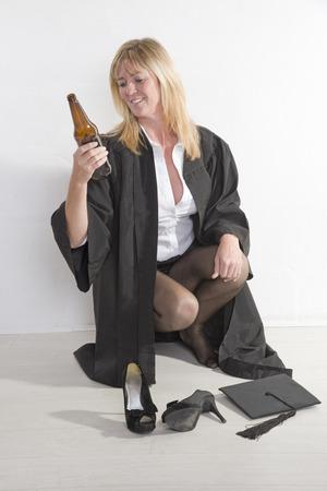 habitual: Mature university student holding beer bottle Stock Photo