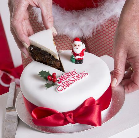 traditiional: Santas helper cutting Christmas cake