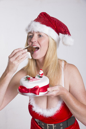 Woman in Santa outfit eating Christmas cake photo