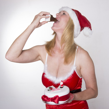 traditiional: Woman in Santa outfit eating Christmas cake Stock Photo