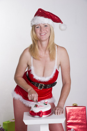 traditiional: Woman in fancy dress cutting Christmas cake Stock Photo