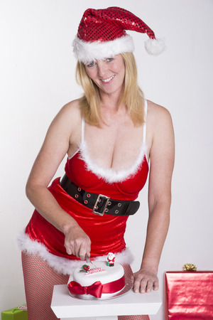 Woman in fancy dress cutting Christmas cake photo