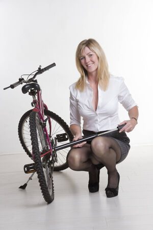 a two wheeled vehicle: Woman inflating the tyre of her bicycle Stock Photo