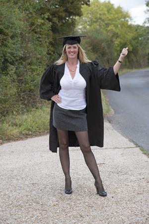 Mature university student on roadside thumbing a left photo
