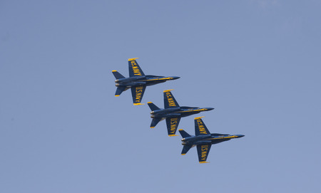 Three US Navy Blue Angels aircraft in flight against a blue sky