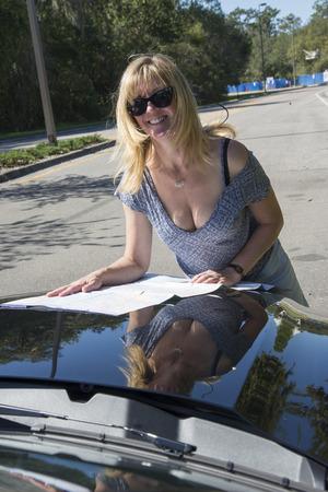 Female driver wearing sun glasses reading map on bonnet of a car Archivio Fotografico