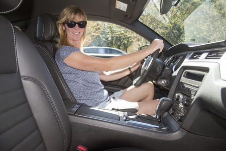 Female driver wearing sun glasses in a lefthand drive American car
